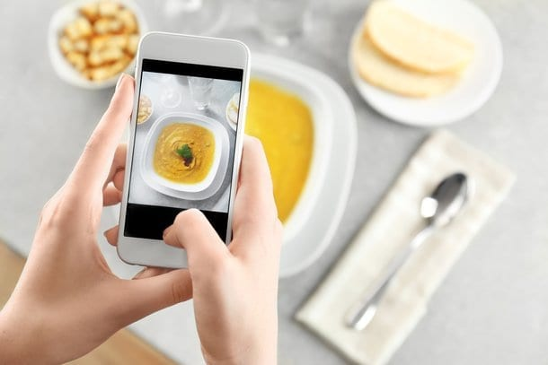 Taking a photo with a camera phone for a food blog.